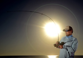 Man fishing with fishing rod and reel during sunrise