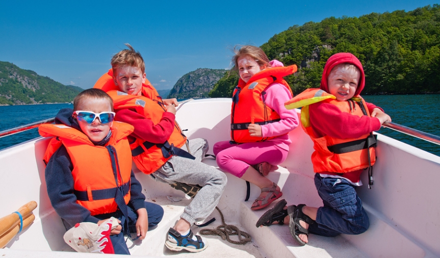 Kids in lifejackets in a boat